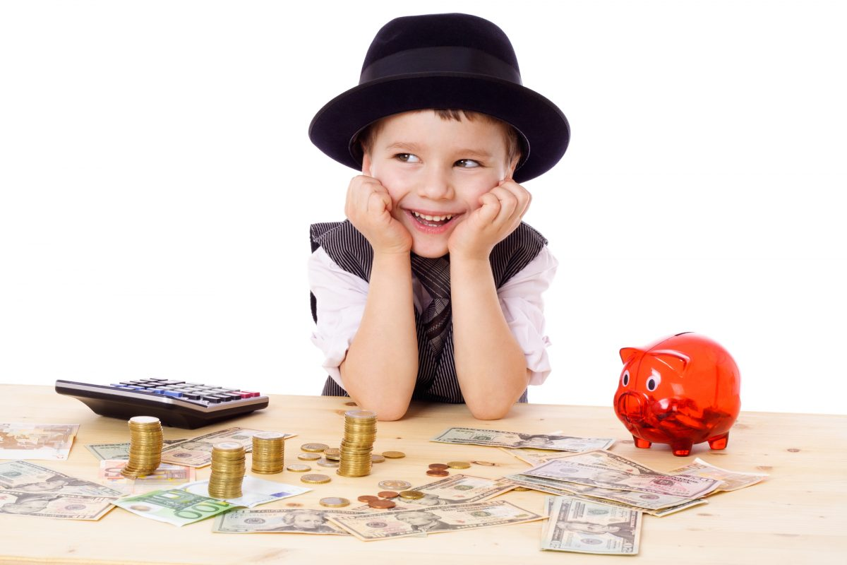 Happy boy in black hat and tie at the table with pile of money, isolated on white